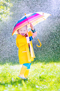 Kind mit Regenschirm im Regen